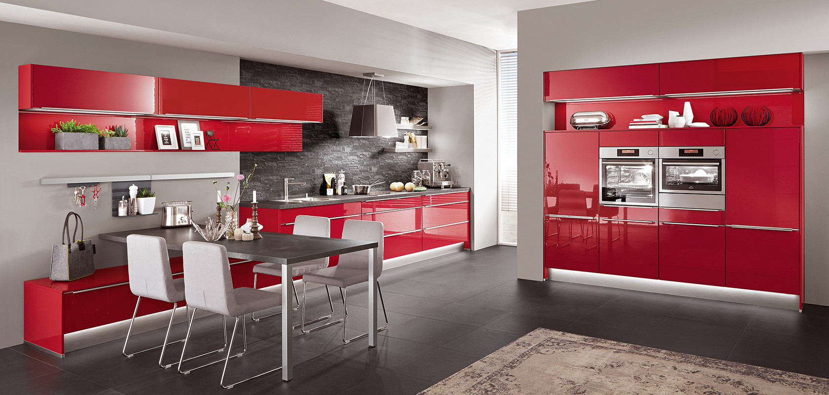 This kitchen in Red high gloss lacquered laminate is a clear affirmation of colour and a real eye-catcher in every flat. Indeed, uprights and top shelves were combined in the same shade and made from the same material. The only accents necessary are the beautifully harmonised stainless steel coloured bar handles and the worktop in Black granite décor.